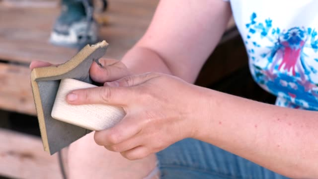Carpenter sanded a wooden parts with sandpaper. Close-up hands.