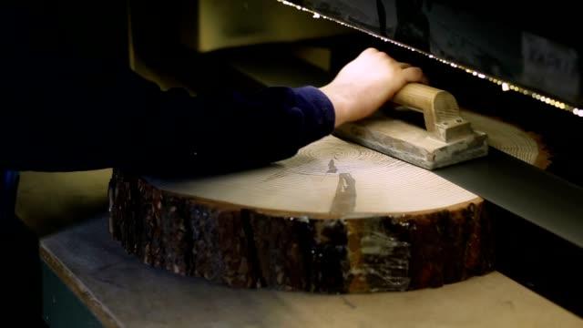 Carpenter sanding log slice with band grinder video