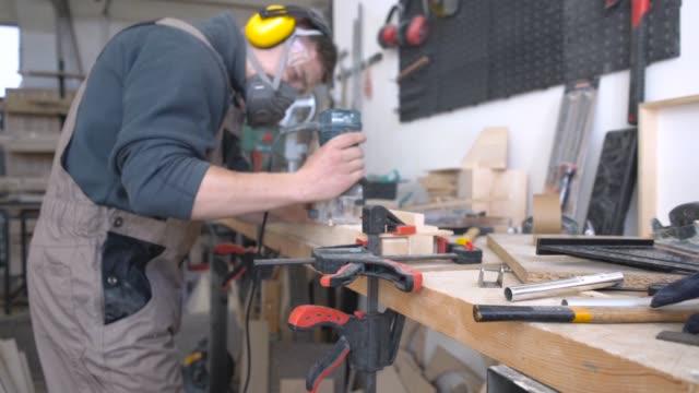 Carpenter sanding wood chunk with hand grinder