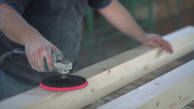 carpenter sanding wood in workshop, close-up shot - levigatrice video stock e b–roll