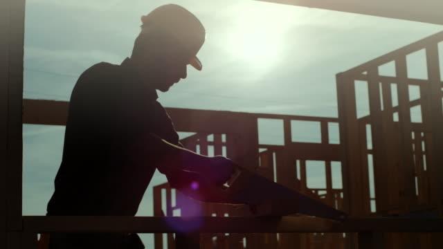 建設現場で大工手木板を鋸を見た - 大工点の映像素材/bロール