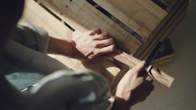 Carpenter sawing wood with hand saw video