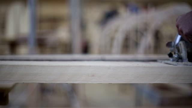 un carpentiere seghe di sconto su una bacheca con un disco visto - segatura video stock e b–roll