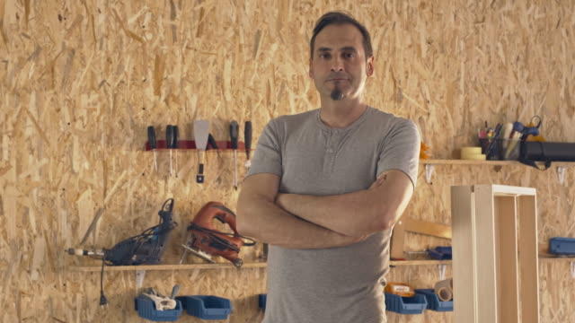 Carpenter stands proudly in his furniture shop video