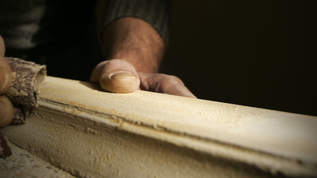 Carpenter using sandpaper to sand wood