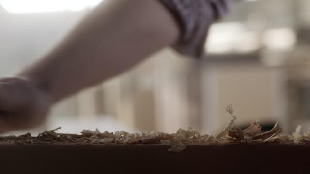 tischler abwischen sägemehl das holzbrett - tischlerarbeit stock-videos und b-roll-filmmaterial
