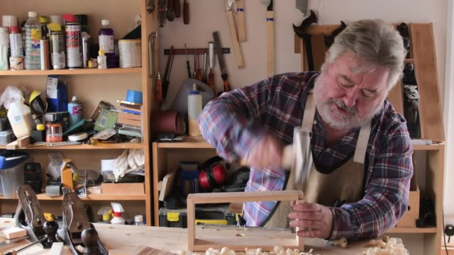 Carpenter working in workshop hammering joint Mature Caucasian male working with wood at workbench. Carpentry shkills. hobbies stock videos & royalty-free footage