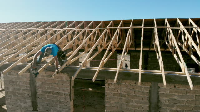 a carpenter working on the roof of a new building - imprenditore edile video stock e b–roll