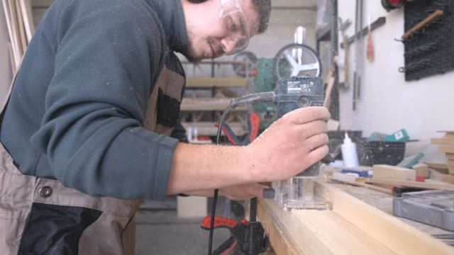Carpenter working on wood plank with hand grinder