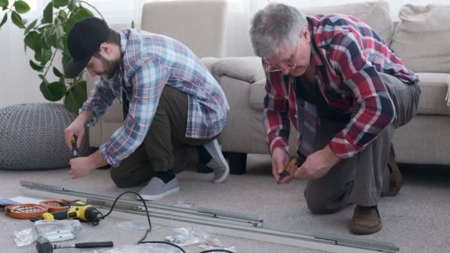 Carpenters using a screwdriver to screw into a metal frame
