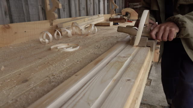 Carpentry work on wood. Carpenter planing a tree, close-up..
