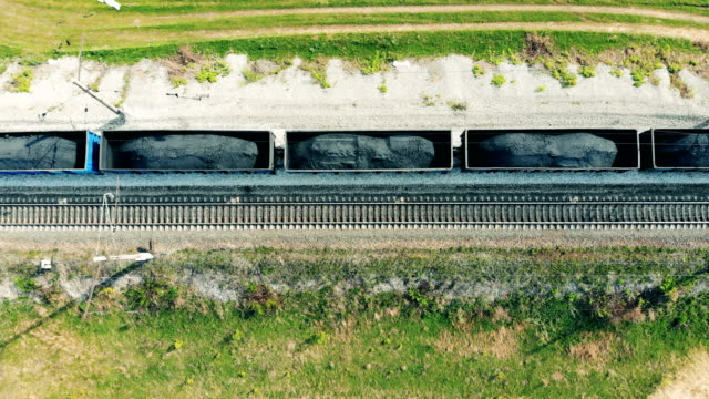 Carriages with coal go on a railroad, top view. One cargo train with carriages goes on a railway, delivering coal. coal stock videos & royalty-free footage