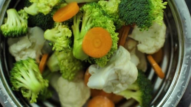 carrot broccoli and cauliflower splashing into water slow motion video - broccolo video stock e b–roll