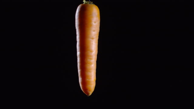 Carrot Floating Isolated on Black Background Close up shot of fresh carrot floating and spinning against black background carrot stock videos & royalty-free footage