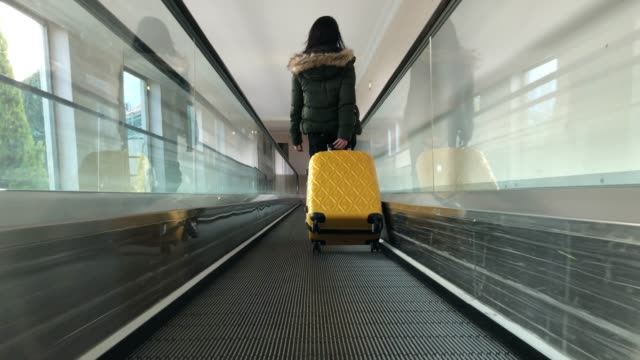 carrying hold suitcase in the airport. - donna valigia solitudine video stock e b–roll