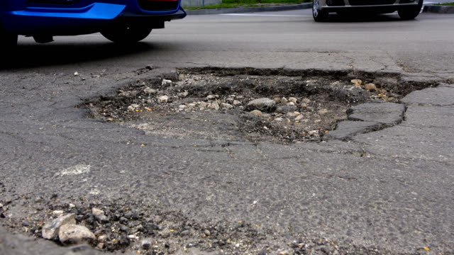 cars and cracked asphalt with holes in the road - foro video stock e b–roll