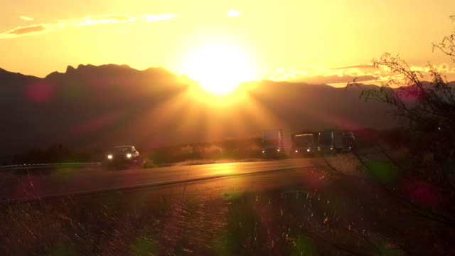 Cars and freight transporting trucks driving on busy highway at golden sunset video