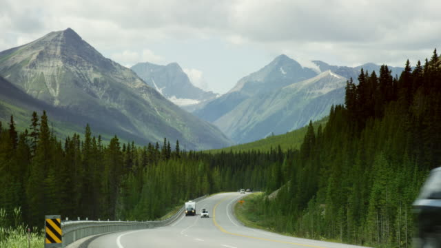 Cars and Other Vehicles Drive along a Treelined Highway in the Canadian Rockies in Alberta, Canada on an Overcast Day