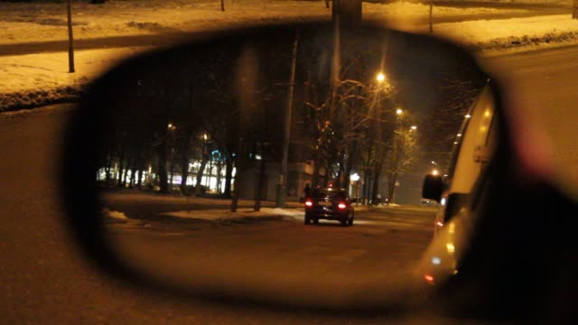 Cars and pedestrians are reflected in the mirror of the side view of the car, in the evening on the city street. Cars and pedestrians are reflected in the mirror of the side view of the car, in the evening on the city street. rear view mirror stock videos & royalty-free footage