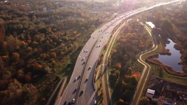 4k aerial: cars and semi truck driving on busy highway across the country in beautiful autumn evening. people on road trip traveling on busy freeway at golden sunset - autobahn video stock e b–roll