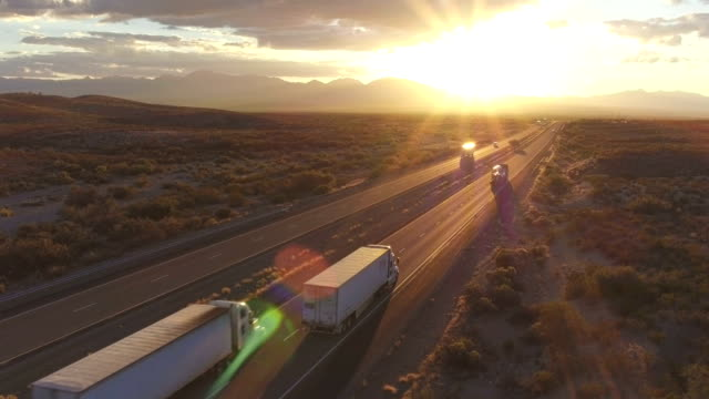 AERIAL: Cars and semi trucks driving on busy highway at summer sunset AERIAL: Cars and freight semi truck driving on busy highway across the country in beautiful summer evening. People on road trip traveling on busy freeway at golden sunset semi truck stock videos & royalty-free footage