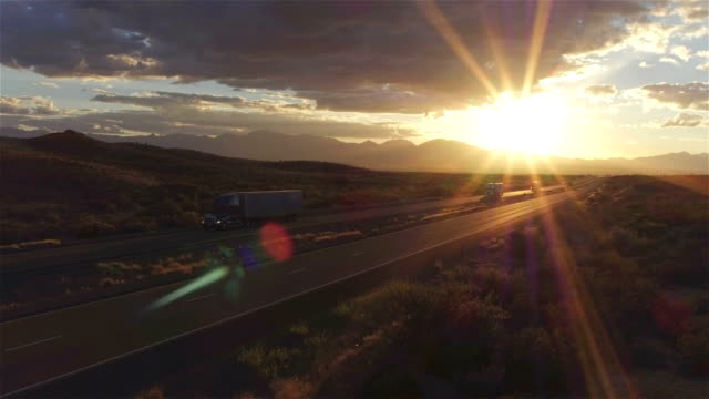 AERIAL: Cars and semi trucks driving on busy highway at summer sunset video