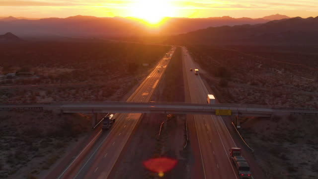 AERIAL: Cars and trucks cross the Mojave desert on a sunny summer morning.