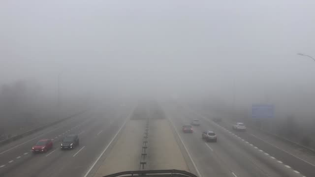 cars and trucks vehicle traffic on a highway on a fog day
