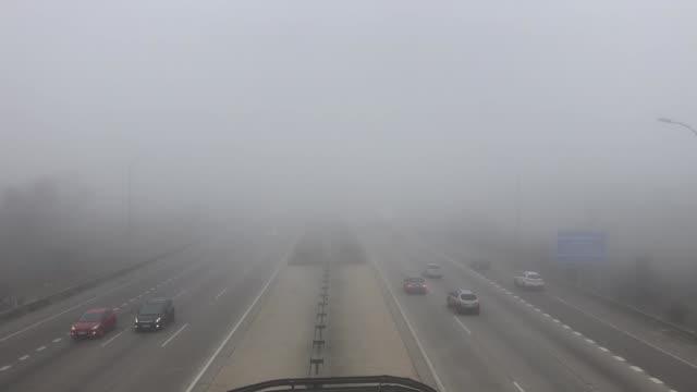 vídeos de stock e filmes b-roll de cars and trucks vehicle traffic on a highway on a fog day - neblina causada por temperatura elevada