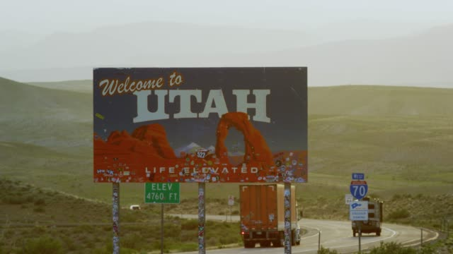 "cars and vehicles drive by as the camera pans from interstate 70 to the ""welcome to utah"" sign on the utah/colorado border (eastern utah) with mountains in the background - utah video stock e b–roll"