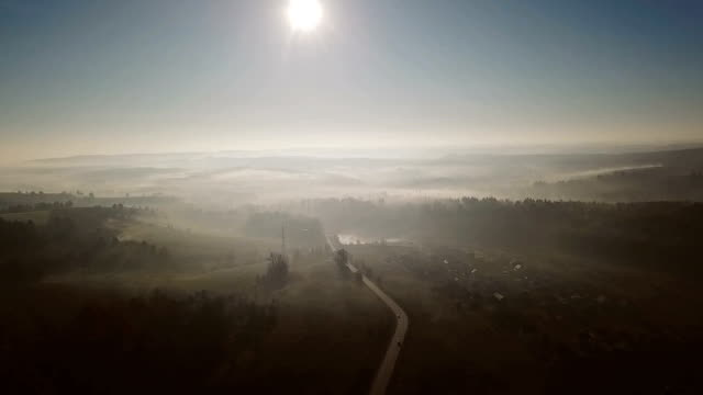 Cars are going on a countryside road. Landscape in the fog. Beautiful nature. Video footage. Aerial top view - video