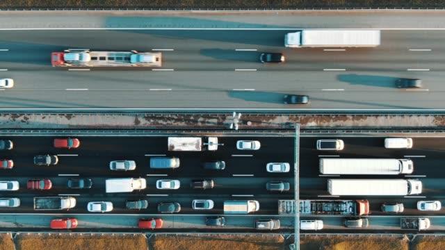 samochody rzucające cienie poruszają się wzdłuż pasa ruchu z lekkim asfaltem - traffic filmów i materiałów b-roll