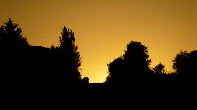 Cars coming down a hill at sunset Cars coming down the hill with the sun hiding between houses and trees at sunset housing logo stock videos & royalty-free footage