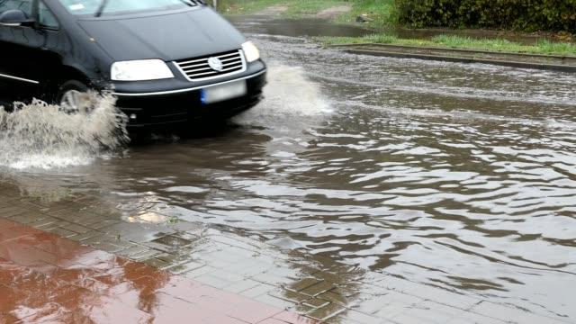 cars crossing flooded urban street - tornado video stock e b–roll
