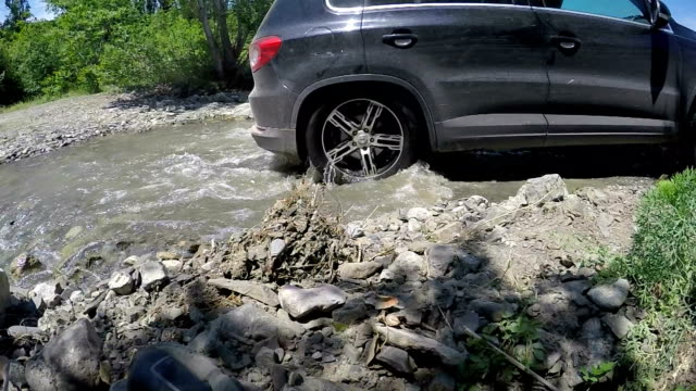Cars crossing mountain creek slow motion video