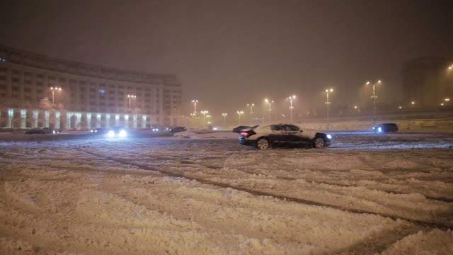 Cars drifting in the parking during a snowstorm. video