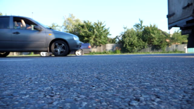 cars drive along highway in countryside. view on the country road. traffic close up. low angle view slow motion - truck tire video stock e b–roll