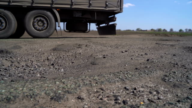 cars drive along the road with potholes - ghiaia video stock e b–roll