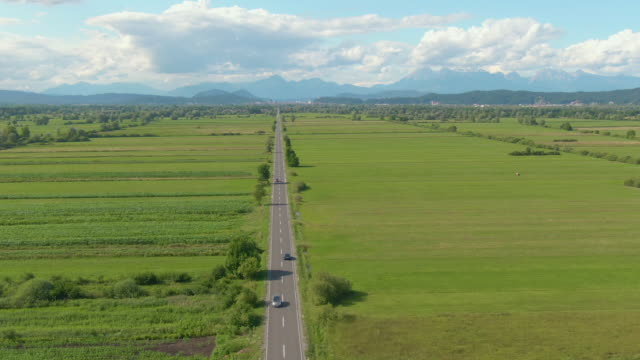 AERIAL: Cars drive up and down the straight road leading through the countryside