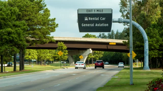 Cars Driving Into Houston Bush IAH Airport Close-up Cars Driving Into Houston George Bush Intercontinental IAH Airport Close up with Overhead Rental Car Signs car rental stock videos & royalty-free footage