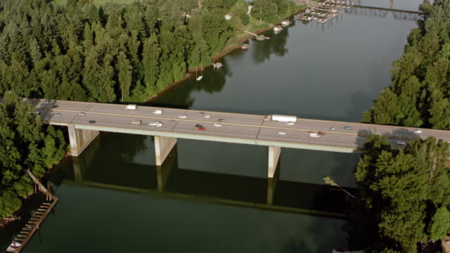 AERIAL Cars driving on a bridge across a river in sunshine video