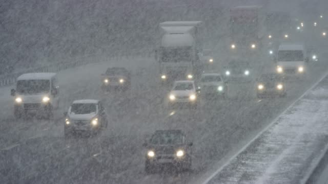 LD Cars driving on a highway in a heavy snow storm