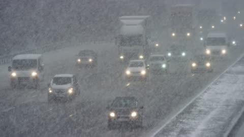vidéos et rushes de ld cars conduisant sur une route dans une tempête de neige lourde - froid