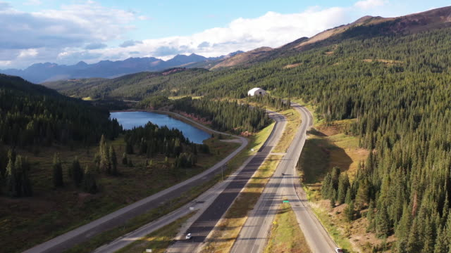 cars driving on colorado freeway with mountains, trees and lake at aerial drone - conifera video stock e b–roll