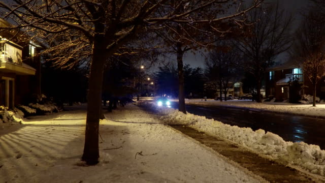 Cars driving slowly, snow covered street in a residential area at night car light trails winter night nature
