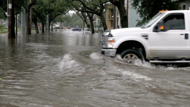 auto che attraversano un incrocio allagato durante un evento di allagamento a nola - uragano video stock e b–roll