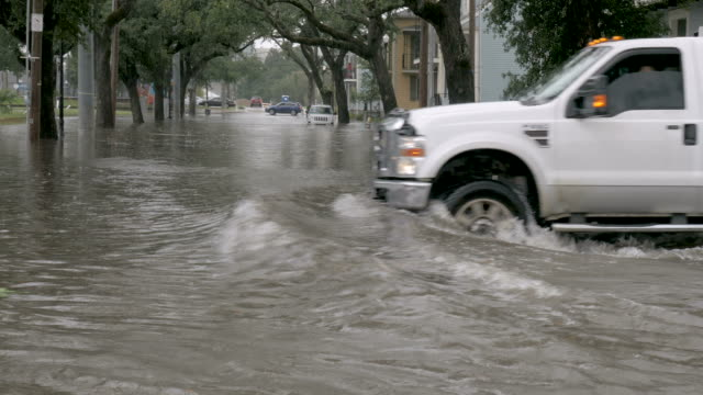 vídeos de stock e filmes b-roll de cars driving through a flooded intersection during a flooding event in nola - resgate