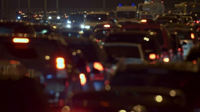 samochody jadące powoli w korku w godzinach szczytu w godzinach wieczornych w dużym mieście. piękny abstrakcyjny widok rozmytych świateł samochodowych. 4k - traffic filmów i materiałów b-roll