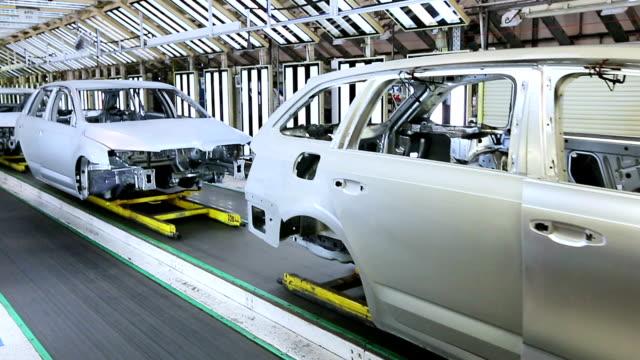 vidéos et rushes de voitures dans une rangée à l'usine de voiture - faire la queue
