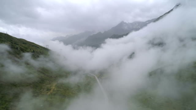 Cars on cloudy mountain road - Aerial 4K Alpe di Maniò, Bedretto, Ticino - Switzerland Drone DJI Phantom 4 PRO 4K - 29.97fps - 21 sec. mountains in mist stock videos & royalty-free footage